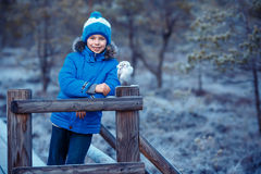 Cute boy with owl toy on shoulder in winter forest Royalty Free Stock Image