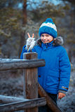 Cute boy with owl toy on shoulder in winter forest Stock Photo