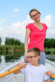 Cute boy paddling with mother in boat. Active happy boy having f. Un with paddling over lake with mother behind Royalty Free Stock Photography