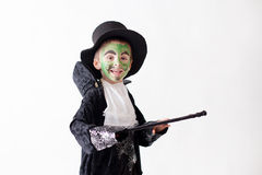 Cute boy with painted face as a a magician and dressed in magician costume, having fun stock photography