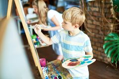 Cute Boy Painting in Art Class. E view portrait of blonde little boy painting on easel enjoying art class with other children in background royalty free stock photography