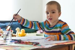 Cute boy painting with brush. Children`s creativity. Boy sitting at table and painting with watercolor paint. Children`s creativity Royalty Free Stock Photos