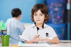 Cute Boy With Paper And Sketch Pen At Desk Stock Images
