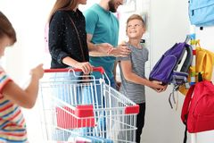 Cute boy with parents choosing backpack royalty free stock images