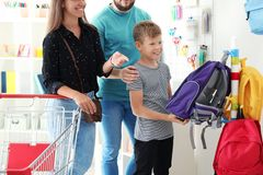 Cute boy with parents choosing backpack royalty free stock photos
