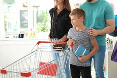 Cute boy with parents choosing school stationery stock photography