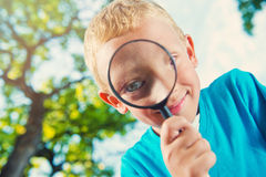 Cute boy in a park with a magnifying glass Royalty Free Stock Image