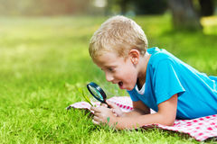 Cute boy in a park with a magnifying glass Royalty Free Stock Photo