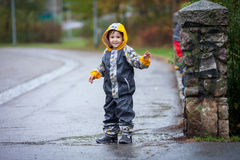 Cute boy in the park, playing in the rain, jumping in puddles Royalty Free Stock Image