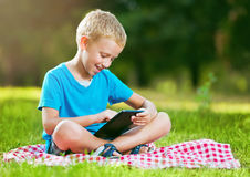 Cute boy in a park using a tablet Royalty Free Stock Image