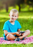 Cute boy in a park using a tablet Stock Photo