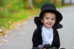 Cute boy in the park, wearing magician costume for Halloween Stock Photos
