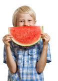 Cute boy peeking behind water melon. A cute happy boy peeking behind a juicy slice of watermelon. Isolated on white stock images