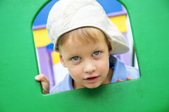 Cute boy peeks through hole at playground Royalty Free Stock Image