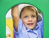 Cute boy peeks through hole at playground Royalty Free Stock Images