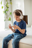 Cute boy with phone and head phones, listening music Stock Photo