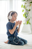 Cute boy with phone and head phones, listening music Royalty Free Stock Photos