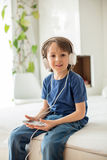 Cute boy with phone and head phones, listening music Stock Photos