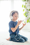 Cute boy with phone and head phones, listening music Royalty Free Stock Photo