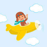 Cute boy pilot flies on a yellow plane in the sky. Air adventure.  Royalty Free Stock Image