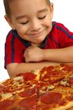 Cute Boy and Pizza. A handsome young smiling boy ready to eat a pepperoni and sausage pizza royalty free stock image
