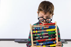 Cute boy playing with abacus in classroom Stock Photography