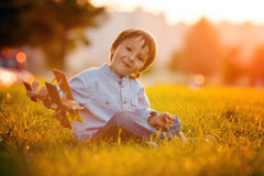Cute boy, playing with airplane on sunset in the park Royalty Free Stock Photos