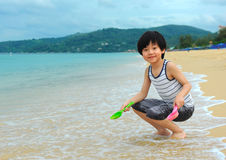 Cute boy playing on the beach Stock Photos