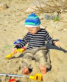 Cute boy playing on a beach Stock Photos