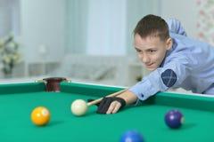 Cute boy playing billiard Stock Photo