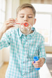 Cute boy playing with bubble wand at home Royalty Free Stock Photo