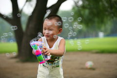Cute boy playing bubbles gun Royalty Free Stock Photo