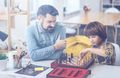 Cute boy playing chess with his father. Men`s club. Bearded father sitting at a desk with his concentrated little son playing chess at home stock photography