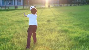Cute boy playing football with football ball on the sunset in the park. s. stock video