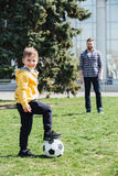 Cute boy playing football with his father in the park Stock Images