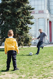 Cute boy playing football with his father in the park Stock Image