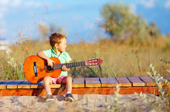 Cute boy playing a guitar on summer field Royalty Free Stock Photography