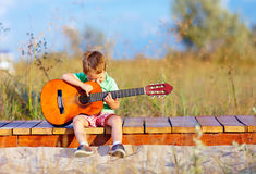 Cute boy playing a guitar on summer field. Portrait of cute boy playing a guitar on summer field Stock Images