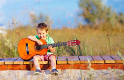 Cute boy playing a guitar on summer field Royalty Free Stock Photo