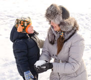Cute boy playing with his mother in the snow Stock Images