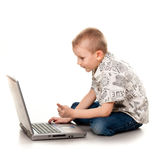 Cute boy playing with laptop Stock Images