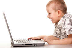 Cute boy playing with laptop Royalty Free Stock Images