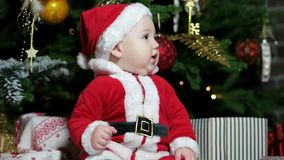 Cute boy playing near the Christmas tree, Little baby dressed in Santa outfits, child in carnival costume plays at home stock footage