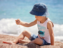 Cute boy, playing with pebbles on the beach Royalty Free Stock Photography