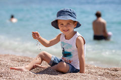 Cute boy, playing with pebbles on the beach Stock Photography