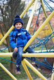 Cute boy, playing on the playground. Springtime Royalty Free Stock Photo