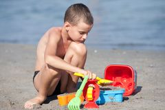 Cute boy playing in sand Stock Images