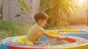Cute boy playing with sand in a sandbox. Cute baby boy playing with sand in a sandbox stock video