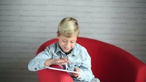 Cute boy playing with a smartphone stock footage