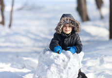 Cute boy playing with snow in the winter park Stock Images